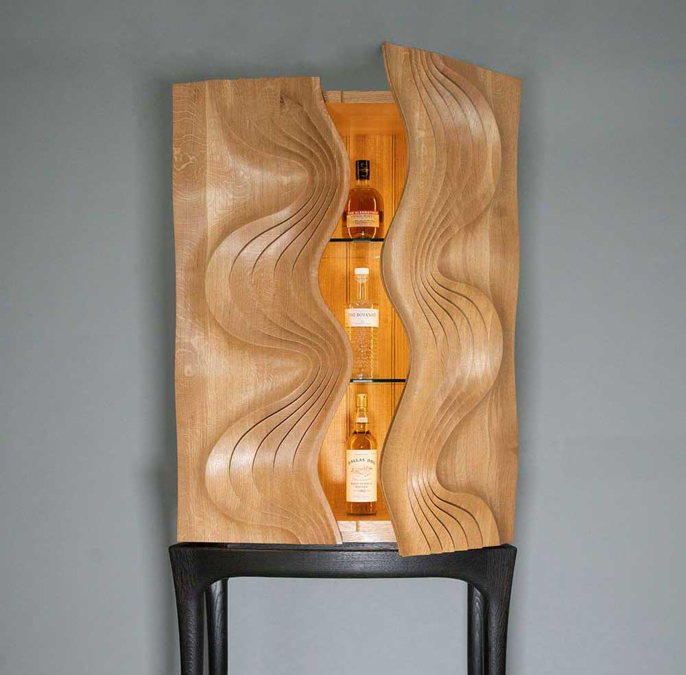 Duke Christie, bow-fronted oak drinks cabinet on a sculpted scorched oak'.