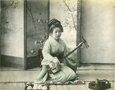 A Japanese woman playing a shamisen