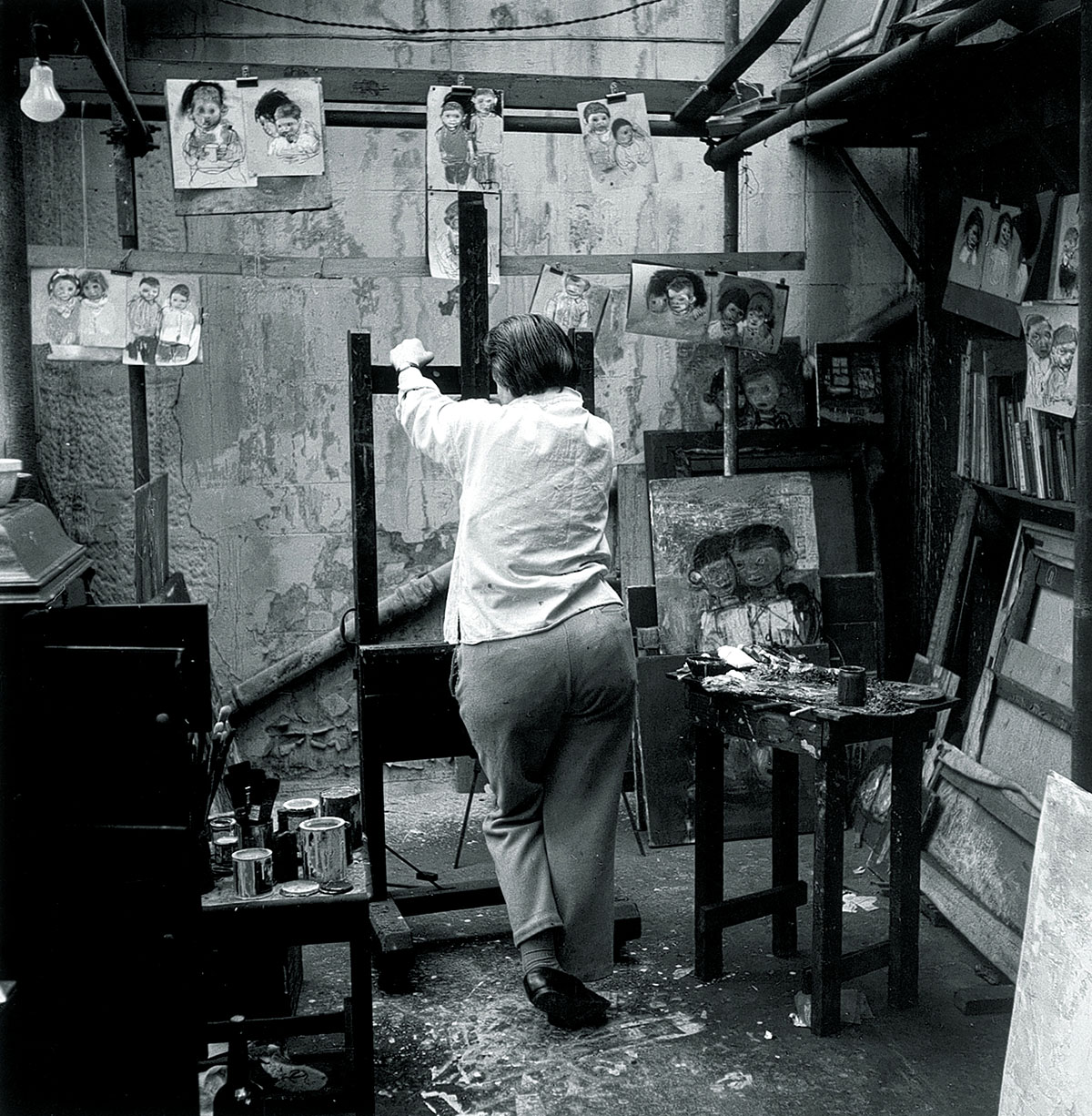 Joan Eardley in her studio at 204 St James Road, Townhead in Glasgow with chalk sketches of children, circa 1950s. Photo estate of Audrey Walker